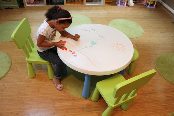 Criança a desenhar na mesa com marcadores para quadro branco da marca