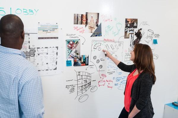 Colaboradores a trocarem ideias junto de uma parede com tiinta idea paint